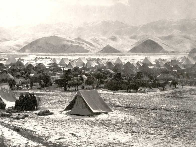 General view of the ABC camping ground at Chaharshamba. Several army tents are mingled with kibitkas. Several picketed horses covered with blankets are visible. A thin layer of snow covers the muddy ground. In the foreground a group of people is sitting close together at a camp fire. Behind them, between two kibitkas, a mile-measuring machine is slightly visible. In the background the snow-covered ridge of the Band-e Turkistan.