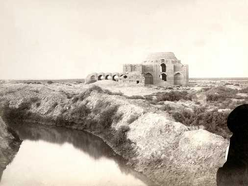 A domed structure made from burned bricks, which was never finished. It consists of a central two-storied building and two single-storied wings. The interpretation is either that it was intended to become a caravan saray or a musalla (religious school). In the foreground a water channel between high dams. On the left side of the building a low enclosure with zickzack bricks defines a platform for prayer.